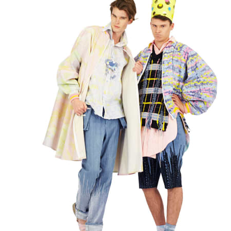 Two male models in denim and pastel clothes; one wears a paper crown.