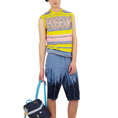 A male model wears a pastel knitted vest that reads