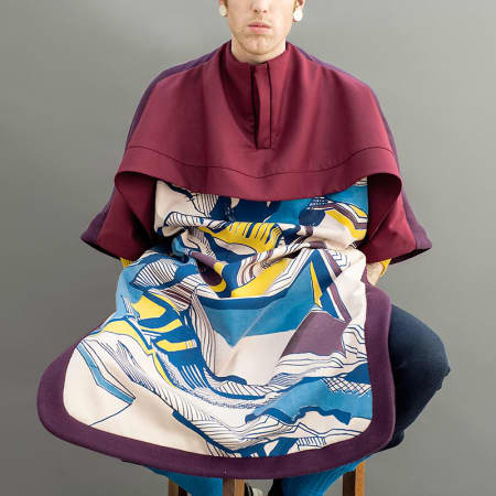 A redhead male model wears a maroon cape with patterned bib.