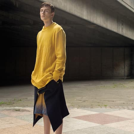 A male model in an oversized yellow jumper and ombre wool shorts.