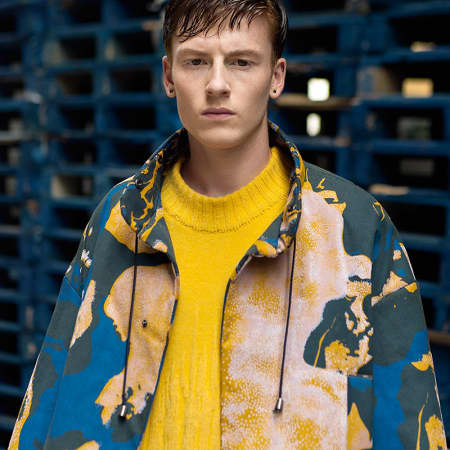 A model in a yellow jumper and yellow and blue camouflage jacket.
