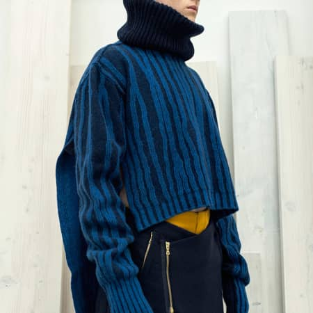 A male model in a knitted black cowl-neck jumper with wiggly blue ribs.