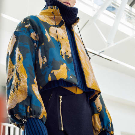 A male model in a yellow and blue camouflage print jacket.