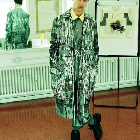 A male model in a long patterned coat with a drawstring waist.