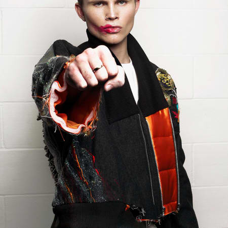 A male model wears an embroidered bomber jacket with exposed orange lining.