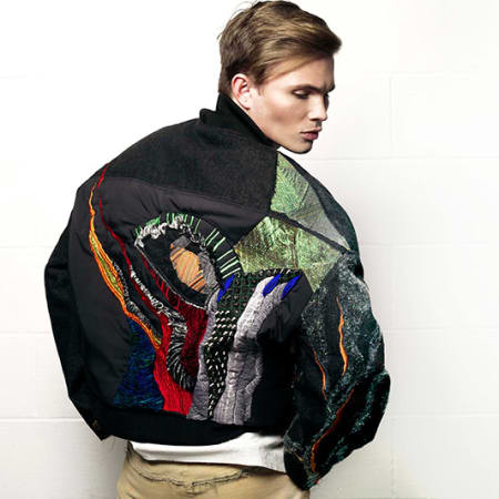 A male model in an embroidered bomber jacket.
