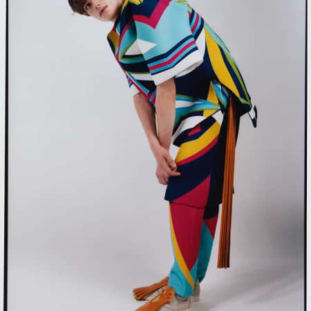 model bending down wearing multi-coloured outfit