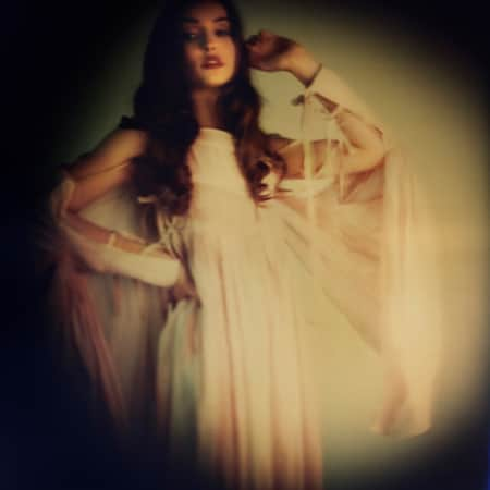 A pin hole camera shot of a model wearing a cream dress with ties.