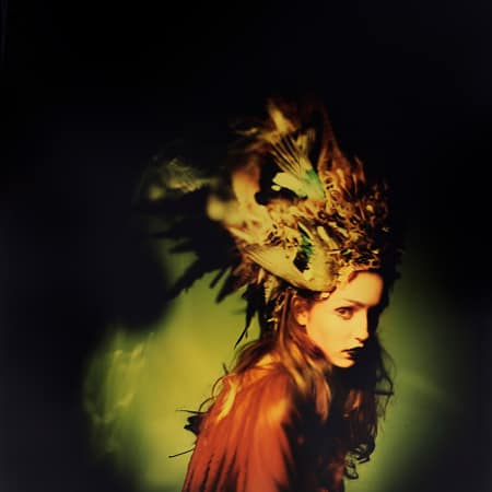 A model wears a feathered headdress, shot using a pin-hole camera