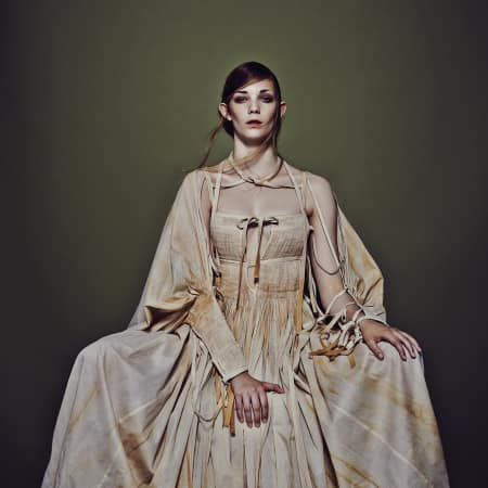 A model sits in a long cream dress with ties