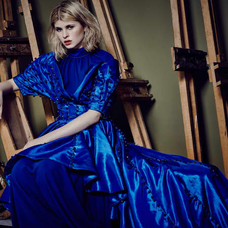 A model sits in a metallic blue gown