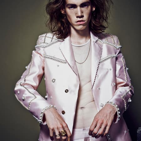 A male model wears a shell pink suit jacket with pearly embroidery