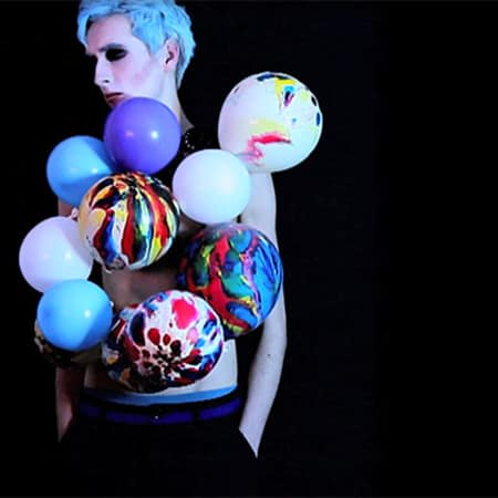 Model with marble patterned balloons attached to his chest, against a dark backdrop.