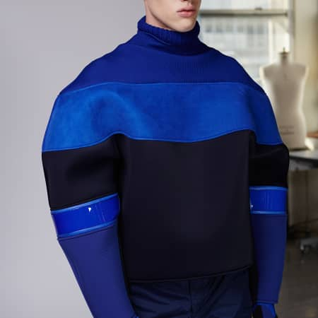 A model in a blue, cocoon shaped jumper with sunglasses on.