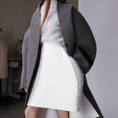 A model in a white and fluffy grey dress with a darker grey oversized coat.