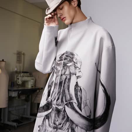 A model wears a pale lilac coat with a mammoth skeleton print and a rounded top hat.