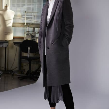 A model wears a long grey coat with pleated chiffon drapes.