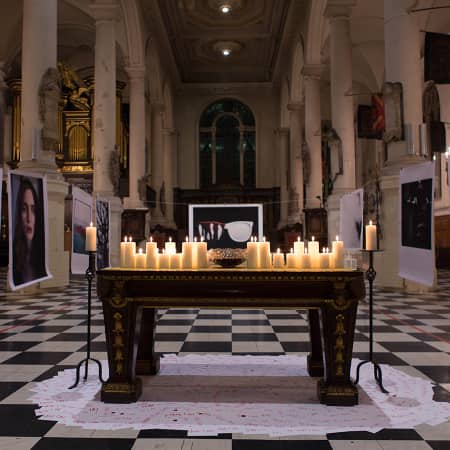 Candles on a table in a church, with blown-up photographs hanging