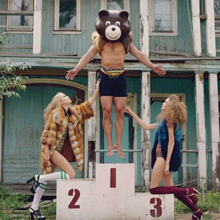 One male model wearing bear's head and two female models holding them up.