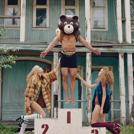 A male model hovers above large couting blocks in a bear's head, with two models holding him up; in front of a house.