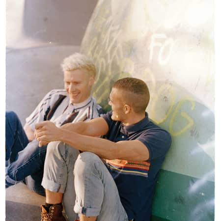 Two men sitting on the ground, against a graffiti wall.