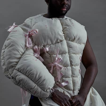 Model wearing pillow and bow outfit