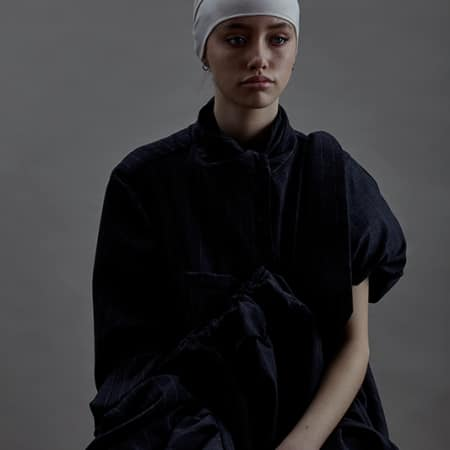 Female model in dark outfit and white headscarf