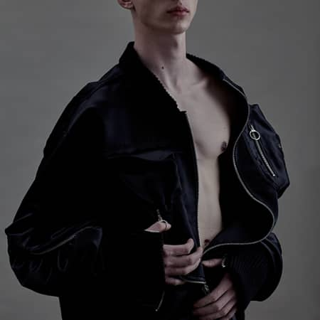 Male model in black jacket with ring pull fastening.