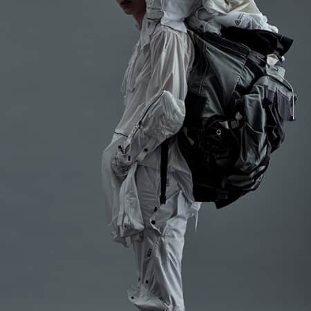 Model in clothing with oversize rucksack on back