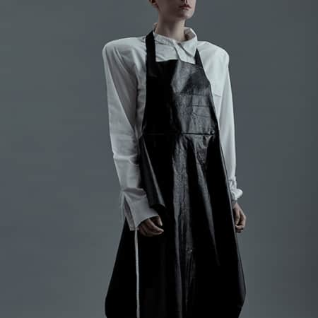 Female model in white shirt and leather pinafore/apron