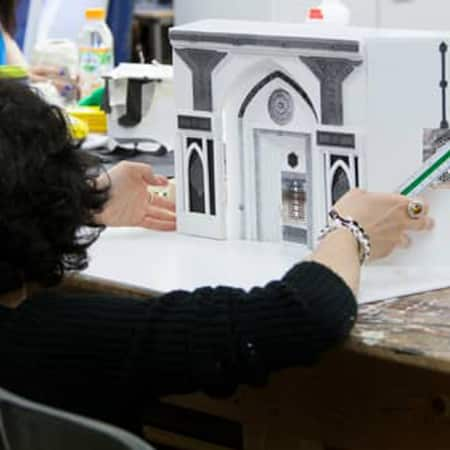 Student working on a foam board model of a set design created in response to a short course brief.