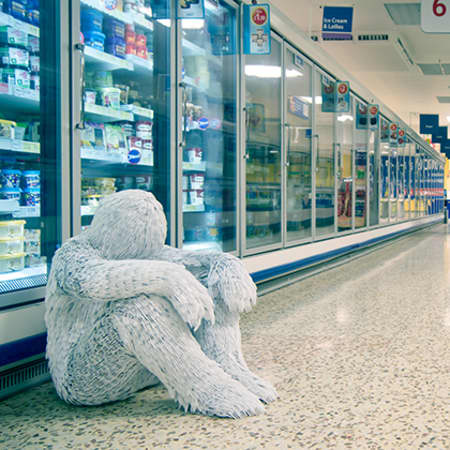Photograph by alumni Laura Thompson, 2012. A person made of white plastic forks sits on the floor of a brightly-lit supermarket.