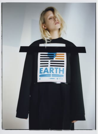 Model wearing black jumper with front printed logo