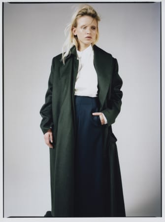 Model wearing green coat with white shirt underneath.