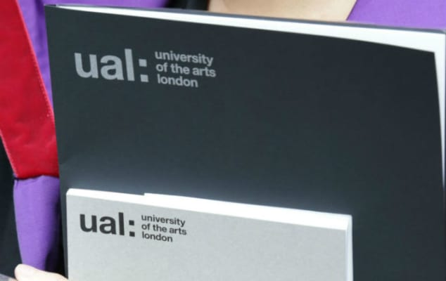 A graduate holding their certificate folder and awards programme from UAL