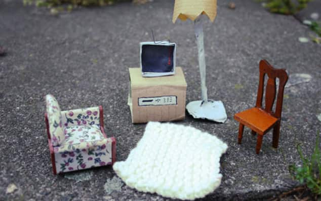 Room for Room by Michael McMillan. Image shows art work – A miniature scene: Two miniature chairs (one wooden, one arm chair) and a cardboard box with a cardboard / paper television next to a lampshade made of paper.