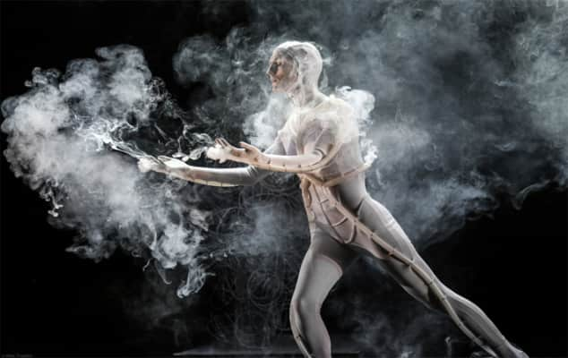 Man in performance costume surrounded by smoke
