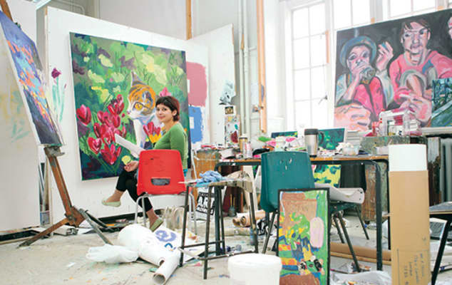 A painter in her studio looking to camera