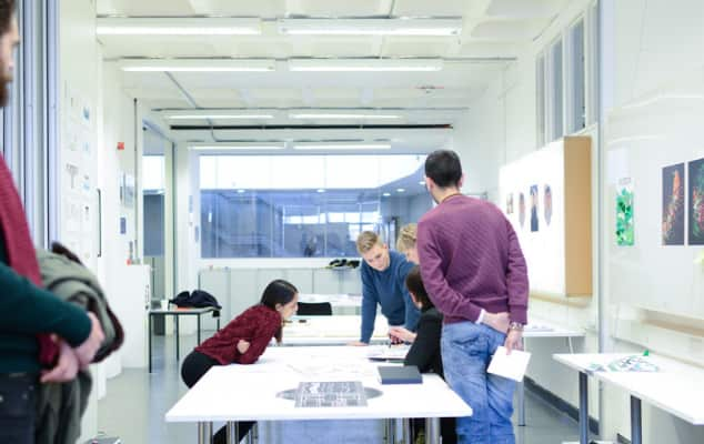 UAL students in a white studio taking instructs from a tutor