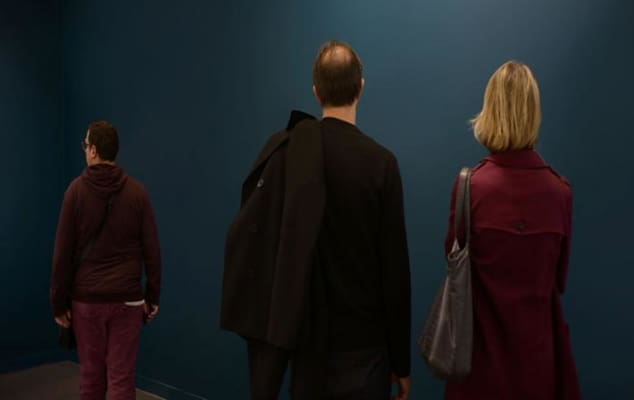 Image of two men and woman backs turned looking at a wall