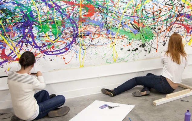 Teenagers working on a group painting. Photograph: