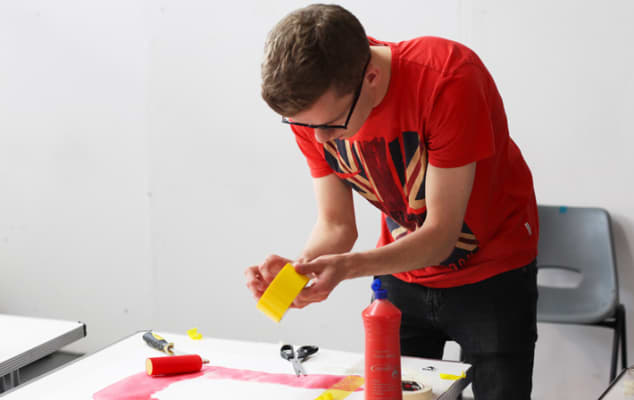 Student applying tape to a graphic piece.