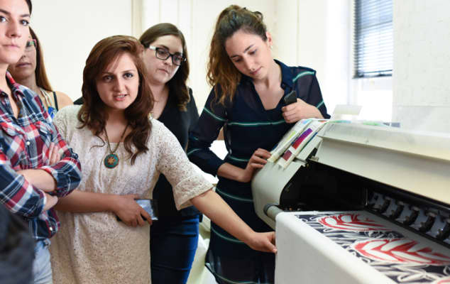 Students gathered around the large digital fabric printer during summer study abroad Digital Textile Design