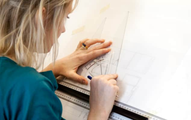Student completing a technical drawing at a drawing board during an interior design course.