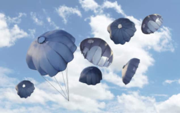 Image of parachutes against a blue sky with white clouds