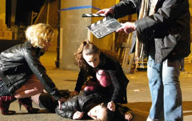 A student lying on the floor while someone stands holding a clapboard above them