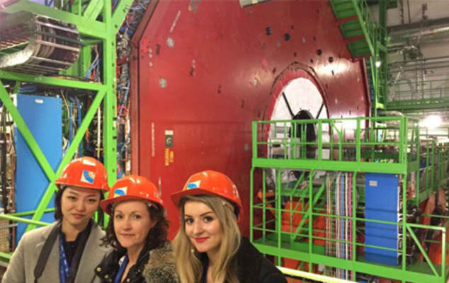 Three young women smiling in red hard hats in front of a large green machine
