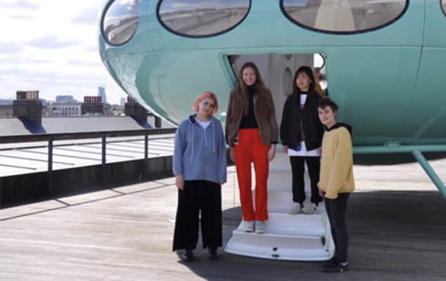 Students standing on the steps of the Futuro House, a temporary structure that looks like a 1950s flying saucer