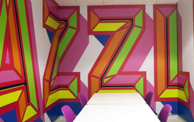 Image of large, brightly coloured graphic letters on the wall of a meeting room