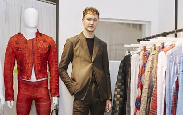 Image of Stefan Cooke standing amongst his clothing designs